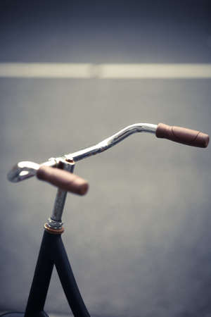 handlebar: Color image of a parked bicycle handlebar on a street. Stock Photo