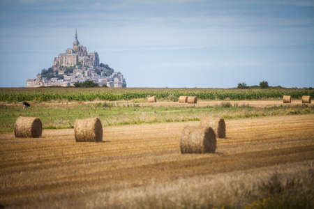 famous industries: Color image some hay rolls in front of Mont Saint Michel in Normandy, France. Stock Photo