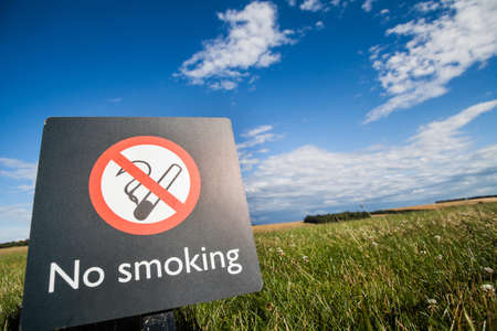 no color: Color image of a No Smoking sign on a on a meadow.