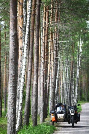 sidecar: Kolga, Estonia - June 21, 2015: Color image of an Ural sidecar motorcycle stopped by the side of the road in a forest.