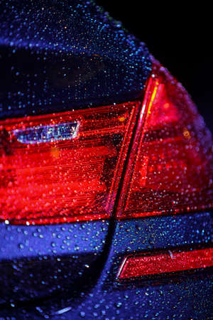 brake: Color image with a cars rear brake light, covered with rain drops.
