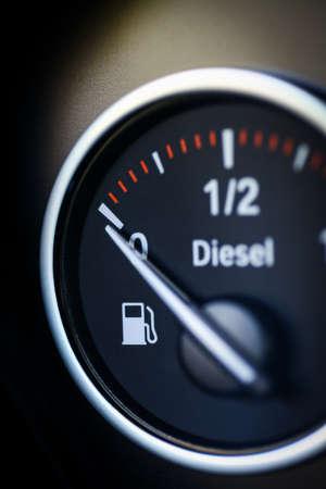 fuel gauge: Close-up shot of a fuel gauge in a car.