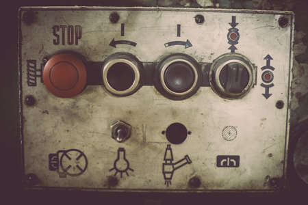 turning operation: Color image of some buttons on a dirty old control panel. Stock Photo