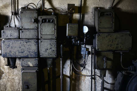 electrical system: Color image of a rusty electrical system on a wall.
