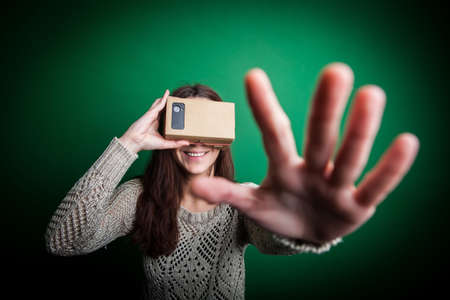 google: Color shot of a young woman looking through a cardboard, a device with which one can experience virtual reality on a mobile phone. Stock Photo