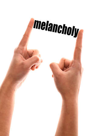 melancholy: Color vertical shot of a of a hand squeezing the word melancholy.