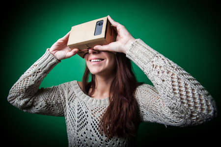 headset woman: Color shot of a young woman looking through a cardboard, a device with which one can experience virtual reality on a mobile phone. Stock Photo