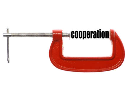 vice: The word cooperation is compressed with a vice. Stock Photo