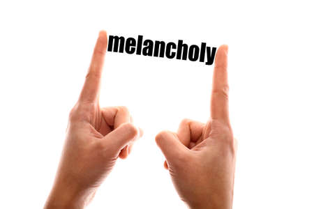 melancholy: Color horizontal shot of a of a hand squeezing the word melancholy.