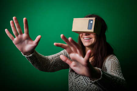 hi: Color shot of a young woman looking through a cardboard, a device with which one can experience virtual reality on a mobile phone. Stock Photo