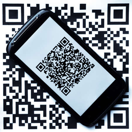 A mobile phone next to a QR code printed on paper. If scanned, the QR code reveals the following text: THIS IS A VERY SIMPLE AND BEAUTIFUL QR CODE. IT WAS GENERATED WITH AN ON-LINE QR CODE GENERATOR.