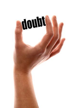 disbelief: Color vertical shot of a hand squeezing the word doubt.