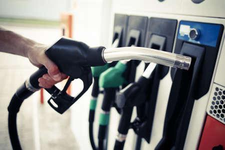 Szczegółowo z ręki trzymającej pompy paliwa na stacji