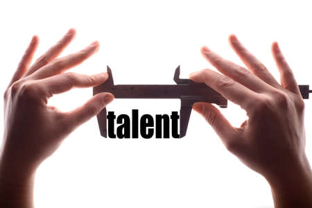 exact: Color horizontal shot of two hands holding a caliper and measuring the word talent.