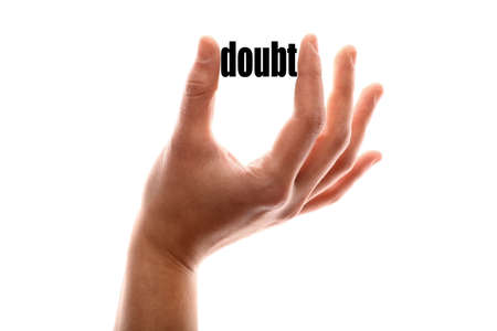 disbelief: Color horizontal shot of a hand squeezing the word doubt.
