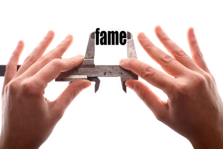 acclaim: Color horizontal shot of two hands holding a caliper and measuring the word fame.