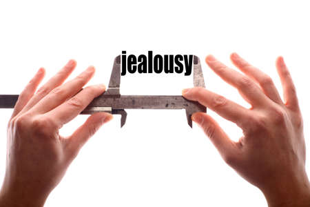 envy: Color horizontal shot of two hands holding a caliper and measuring the word jealousy.