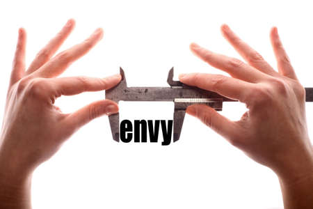 malice: Color horizontal shot of two hands holding a caliper and measuring the word envy. Stock Photo