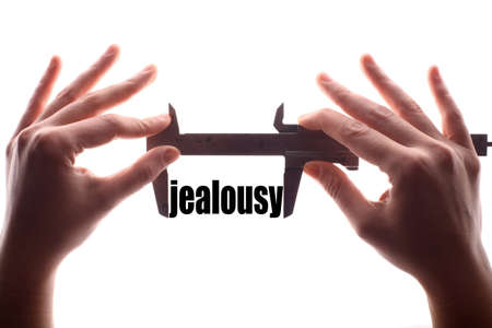 jealousy: Color horizontal shot of two hands holding a caliper and measuring the word jealousy.