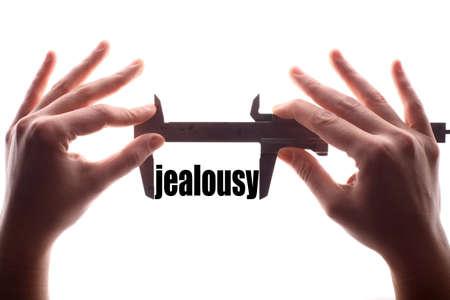 """celos: tiro horizontal del color de dos manos que sostienen una pinza y la medición de la palabra """"celos""""."""