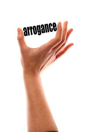 arrogance: Color vertical shot of a of a hand squeezing the word arrogance.