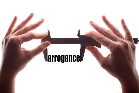 """arrogancia: tiro horizontal del color de dos manos que sostienen una pinza y la medición de la palabra """"arrogancia""""."""