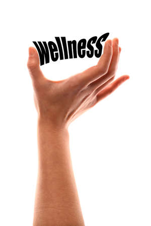 vertical wellness: Color vertical shot of a of a hand squeezing the word wellness. Stock Photo