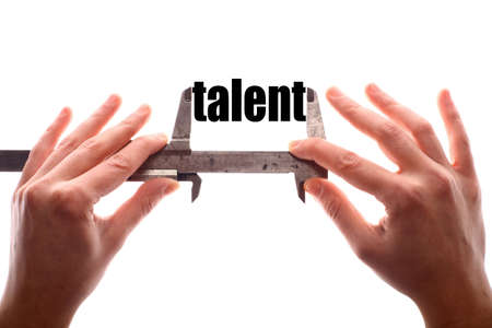 qualified: Color horizontal shot of two hands holding a caliper and measuring the word talent.