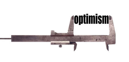 optimism: Color horizontal shot of a caliper and measuring the word optimism.