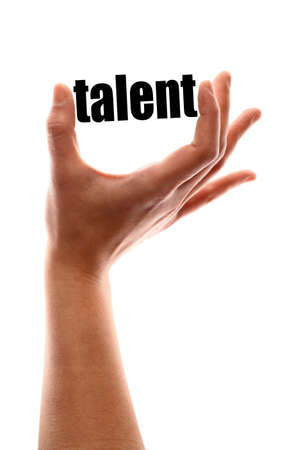 talented: Color vertical shot of a hand squeezing the word talent.