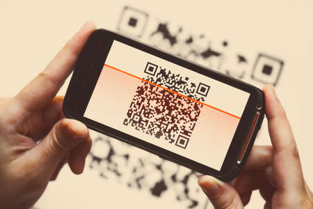 Two hands holding a mobile phone scanning a QR code