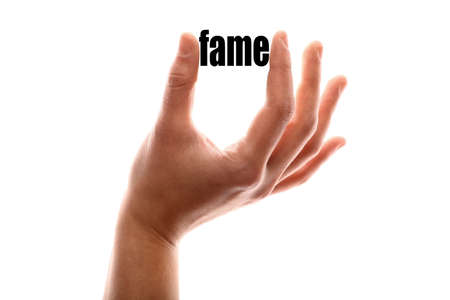 renown: Color horizontal shot of a hand squeezing the word fame.