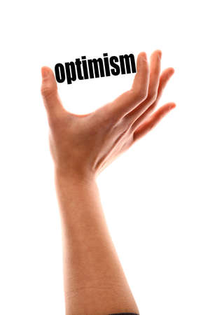 optimism: Color vertical shot of a of a hand squeezing the word optimism. Stock Photo