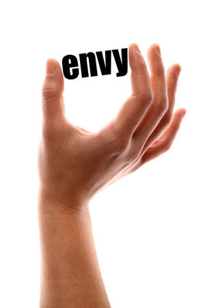 malice: Color vertical shot of a hand squeezing the word envy.