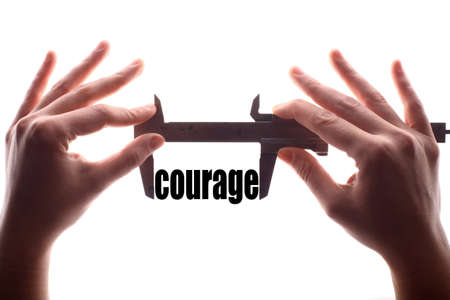 courage: Color horizontal shot of two hands holding a caliper and measuring the word courage.