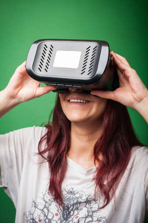 which one: Color shot of a young woman looking through some VR glasses, a device with which one can experience virtual reality on a mobile phone.