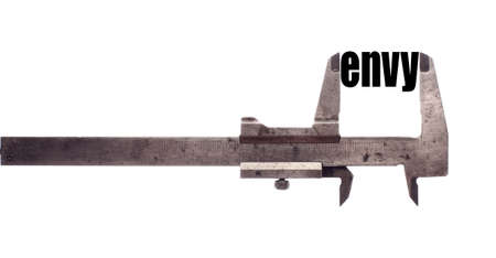 malice: Color horizontal shot of a caliper measuring the word envy.