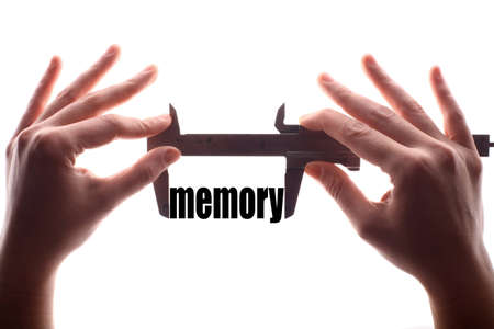 amnesia: Color horizontal shot of two hands holding a caliper and measuring the word mermory.