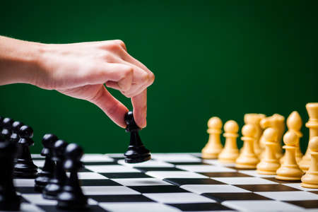 chess piece: Close-up image of a chess board with chess pieces and a human hand.