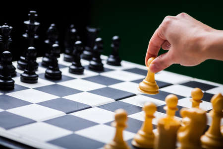 battle plan: Close-up image of a chess board with chess pieces and a human hand.