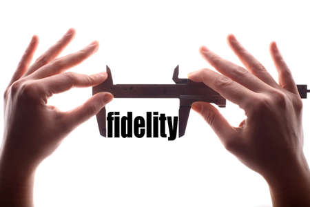 fidelity: Color horizontal shot of two hands holding a caliper and measuring the word fidelity.
