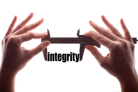 decency: Color horizontal shot of two hands holding a caliper and measuring the word integrity.