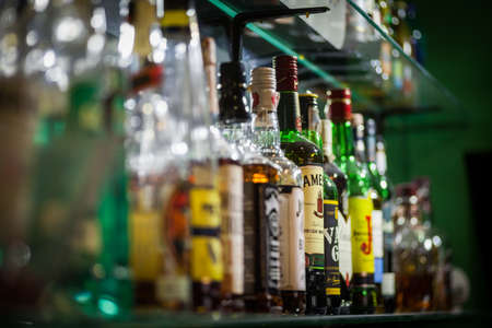 Bucharest, Romania - March 26, 2016: Several types of bottled alcohol are displayed on some shelves in a pub in Bucharest, Romania. 에디토리얼