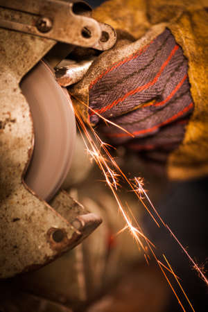 working hands: Color image of a hand polishing at a grinder. Stock Photo