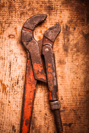adjustable: Color image of an adjustable wrench on a wooden plank.