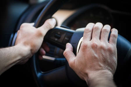 honking: Color image of a hand honking the horn inside a car.