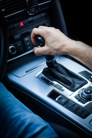 gearstick: Detail of a hand pulling an automatic gear shifter in a new car.