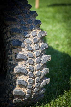 knobby: Color close up of some muddy knobby car tires.