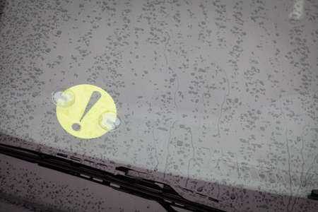 beginner: Color image of a beginner driver sign stuck on a cars windshield.