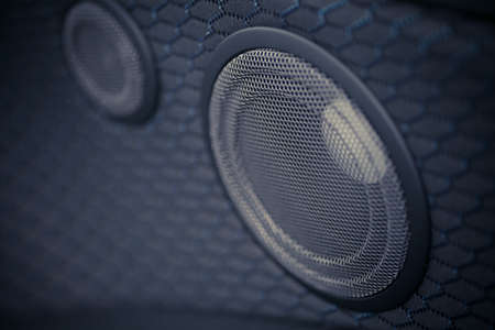 Close up shot of two round speakers in a car.